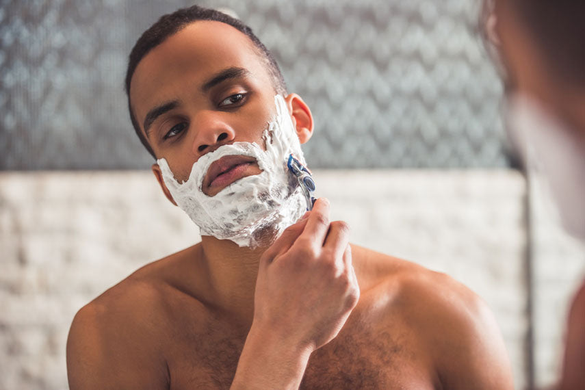 man shaving with razor and cream