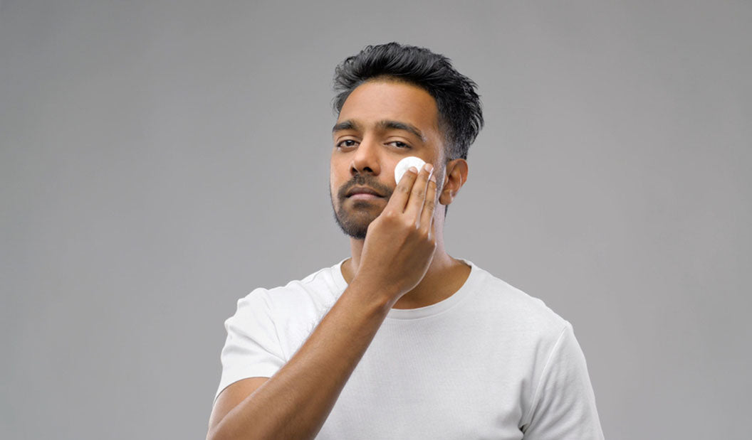 man toning face with cotton pad