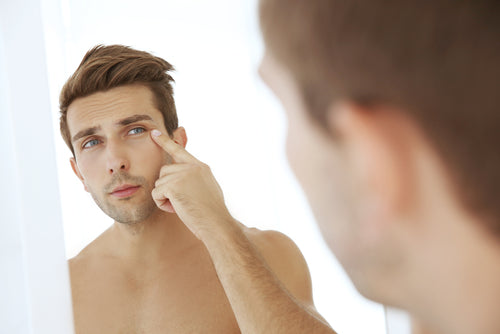 man checking face in mirror