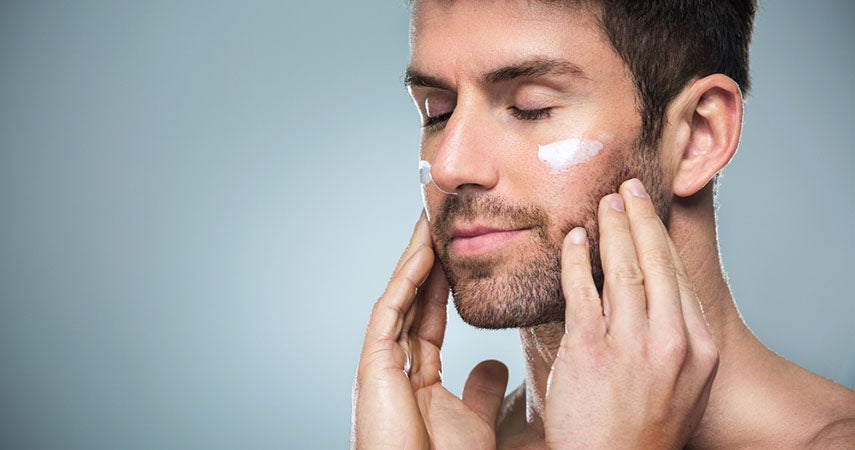 man using cream under eyes