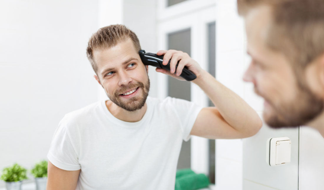 man using hair clippers