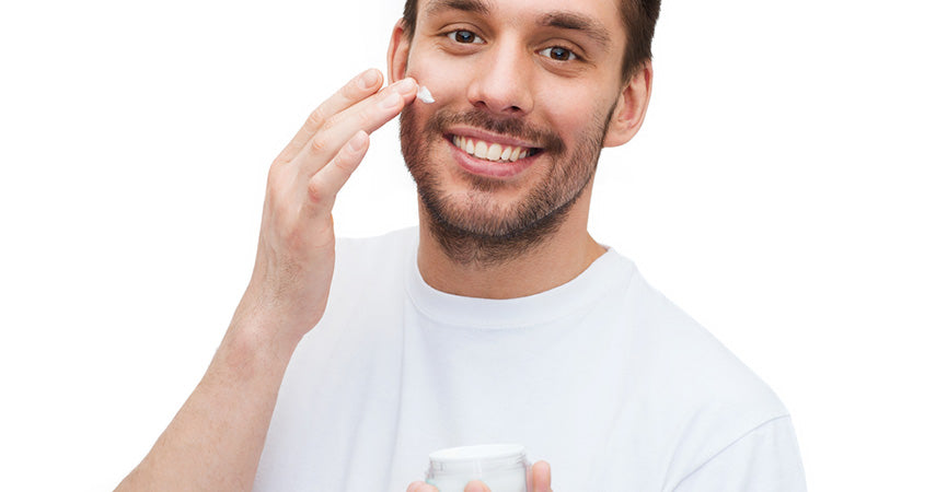 man using jar of cream on face