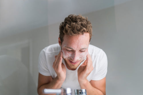 man washing face with facial cleanser