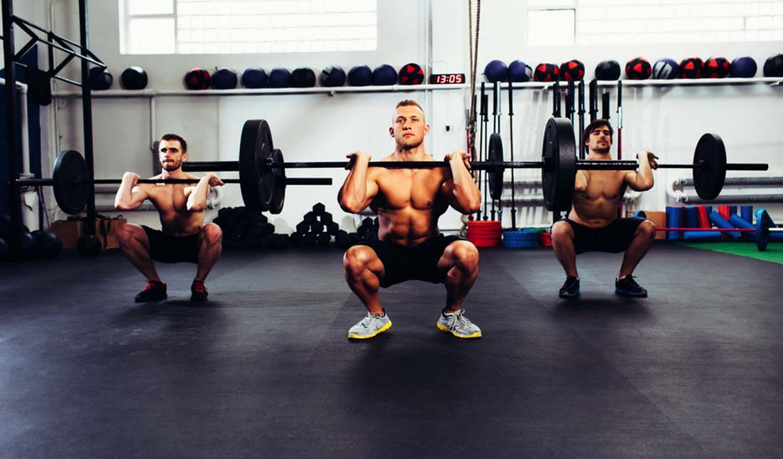 trio of men doing squats with weights