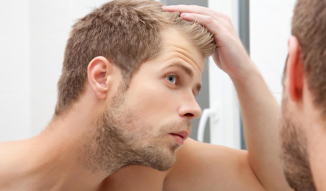 unshaven man looking in mirror
