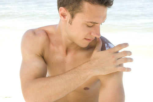 Attractive young man with sunblock at the beach