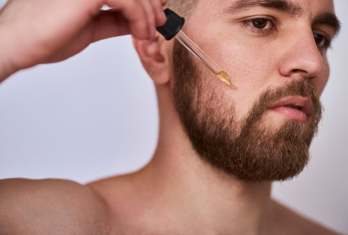 man applying beard oil with pipette