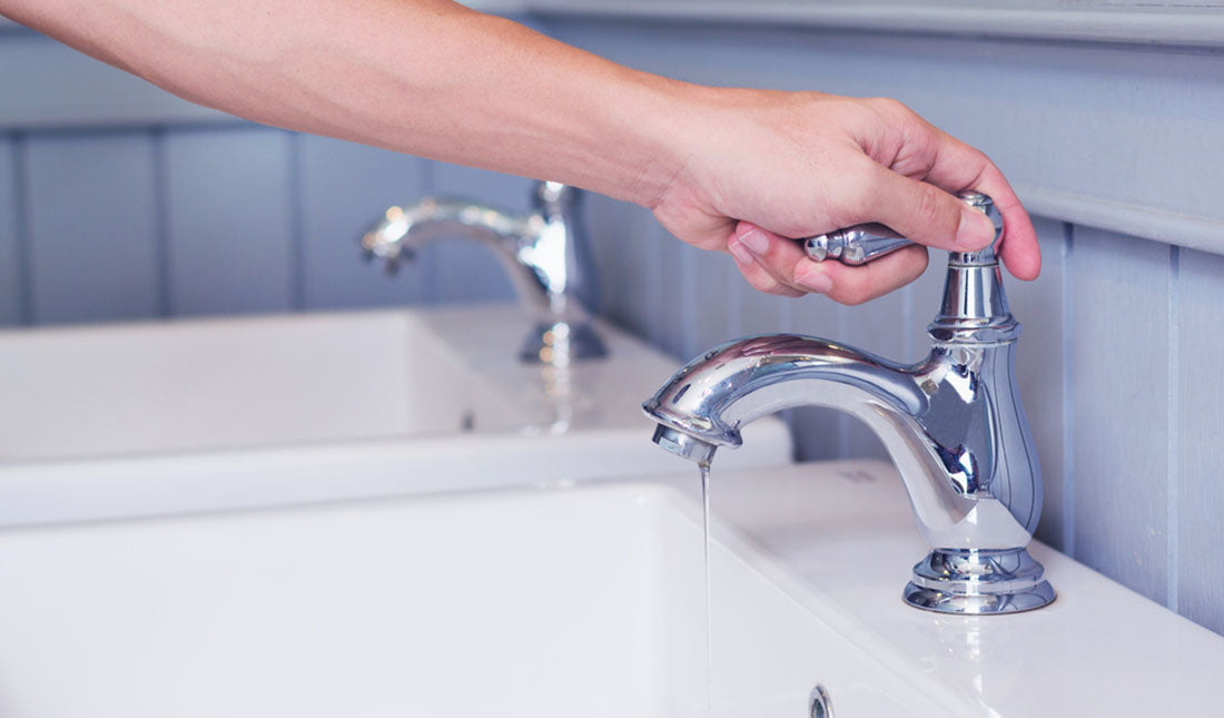 hand turning faucet on
