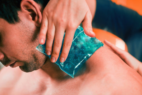 holding blue ice pack on neck