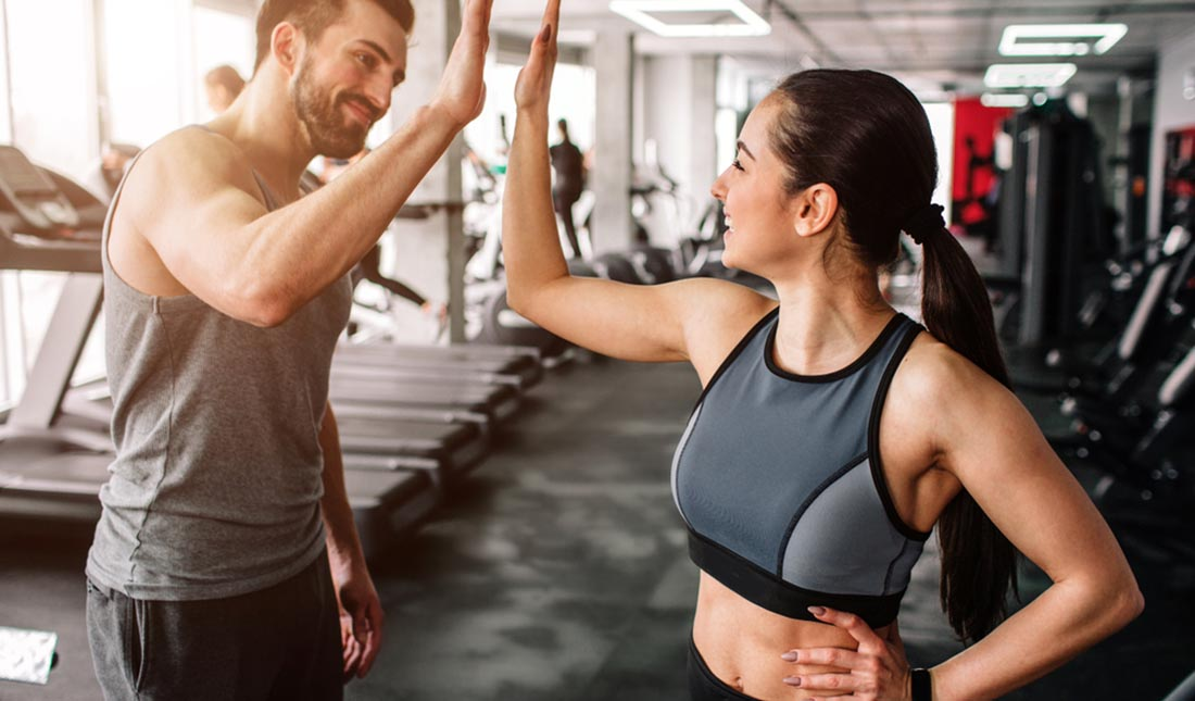 man and woman high five at gym