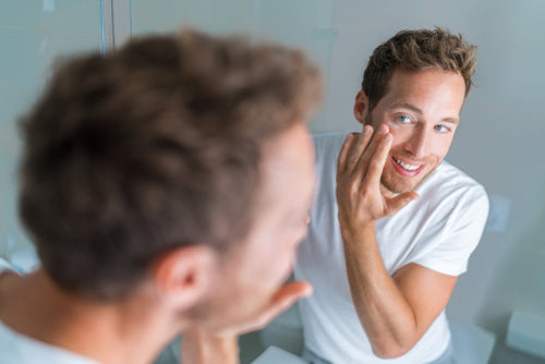 man applying face wash in mirror