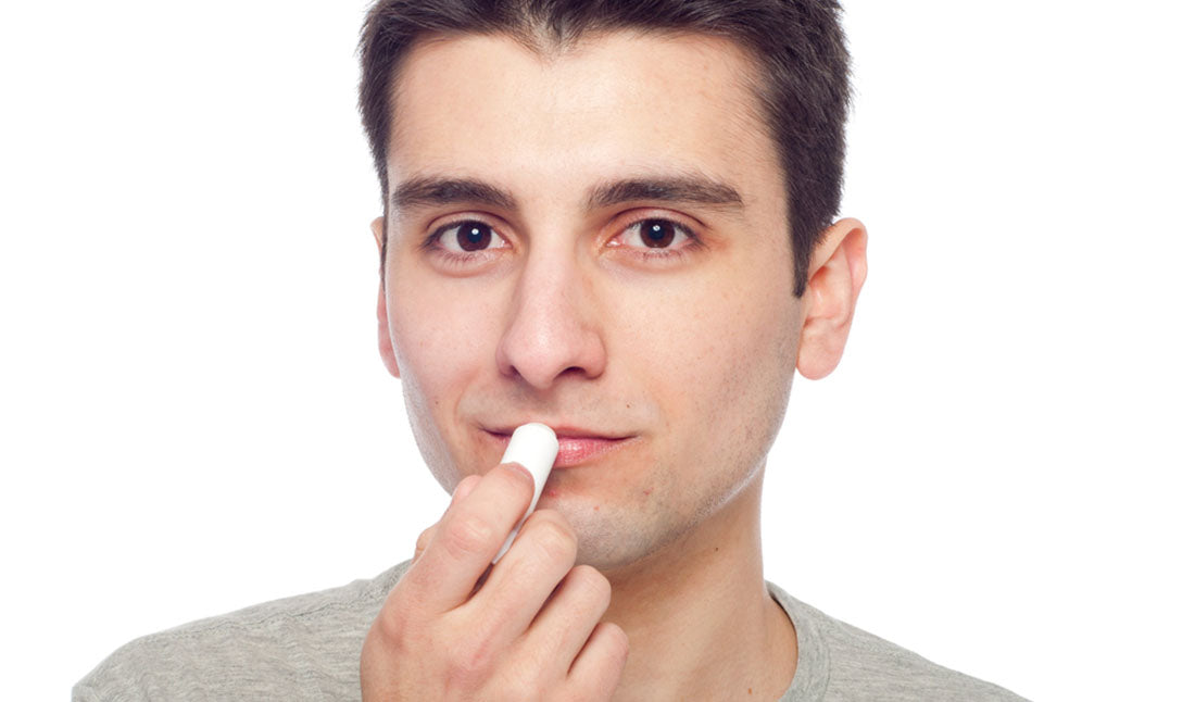 man applying lip balm