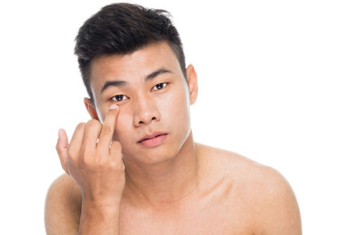 man applying under eye cream