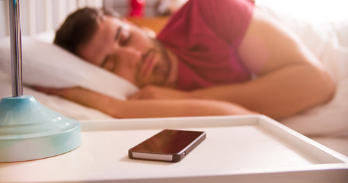 sleeping man using mobile phone alarm