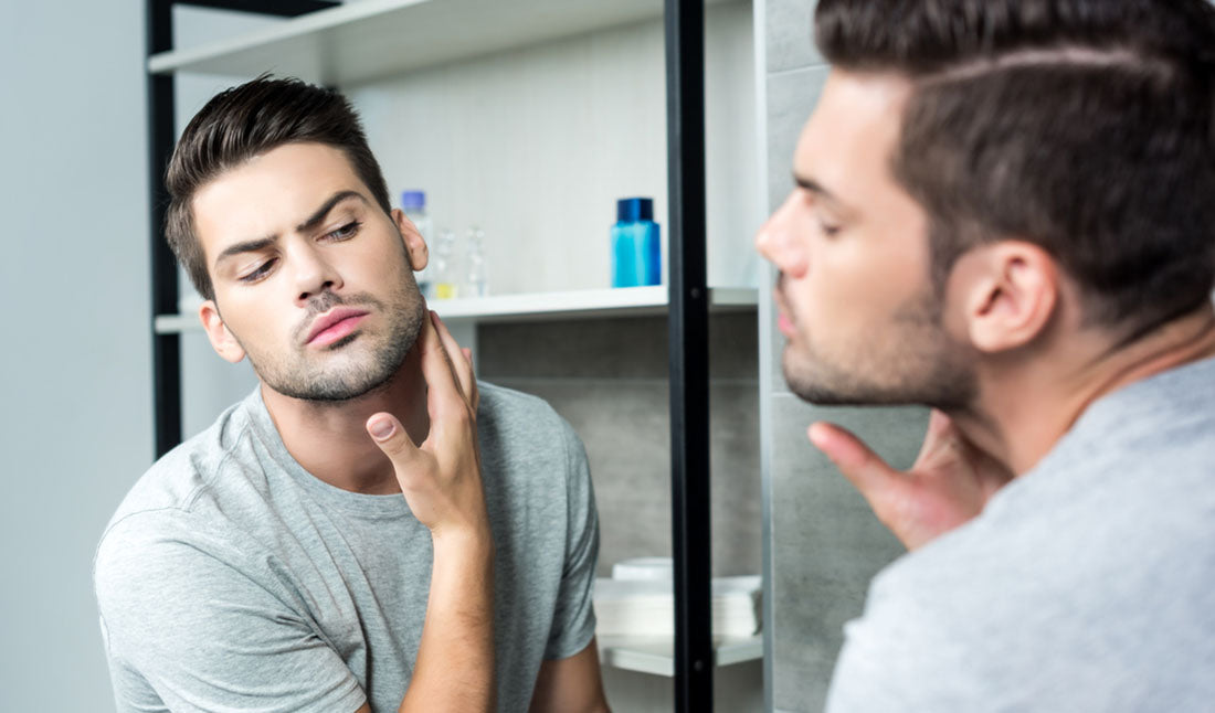 man checking beard growth in mirror