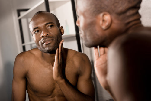 man checking skin in bathroom mirror