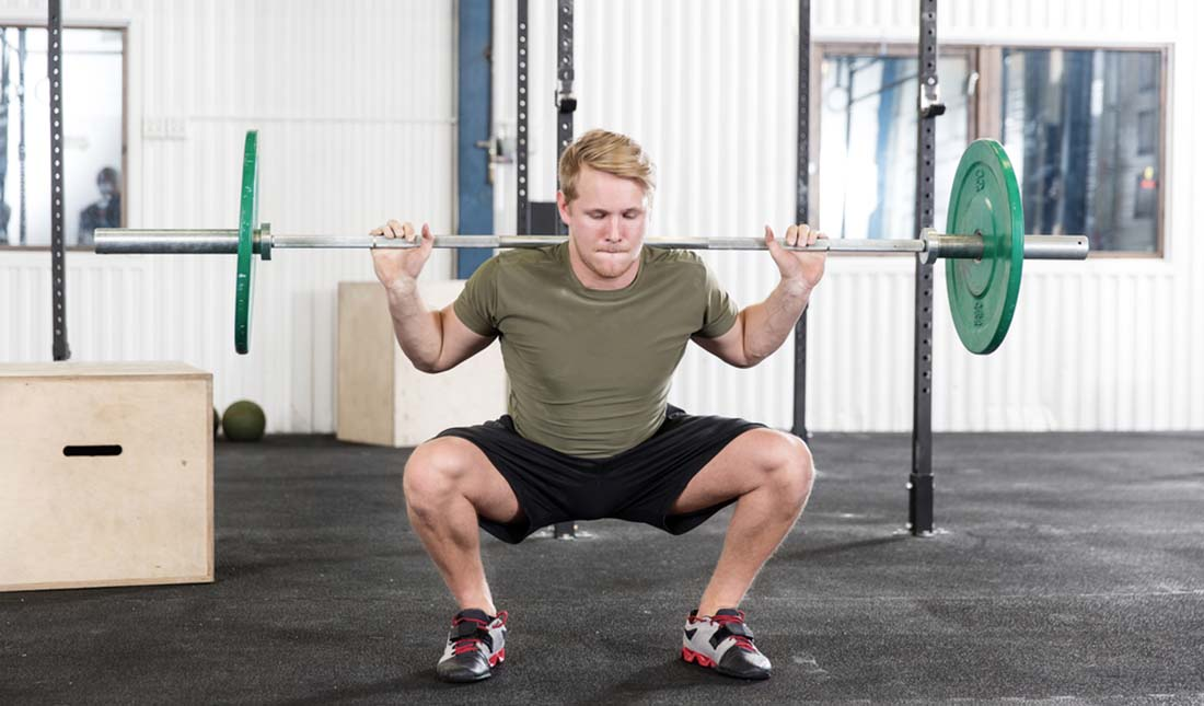 man doing barbell squat press