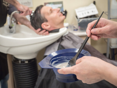 man getting hair dyed at barber shop