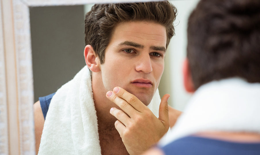 man in mirror looking at face