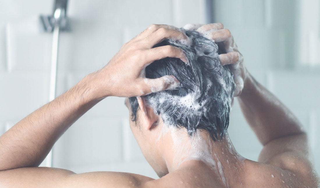 man massaging shampoo in shower