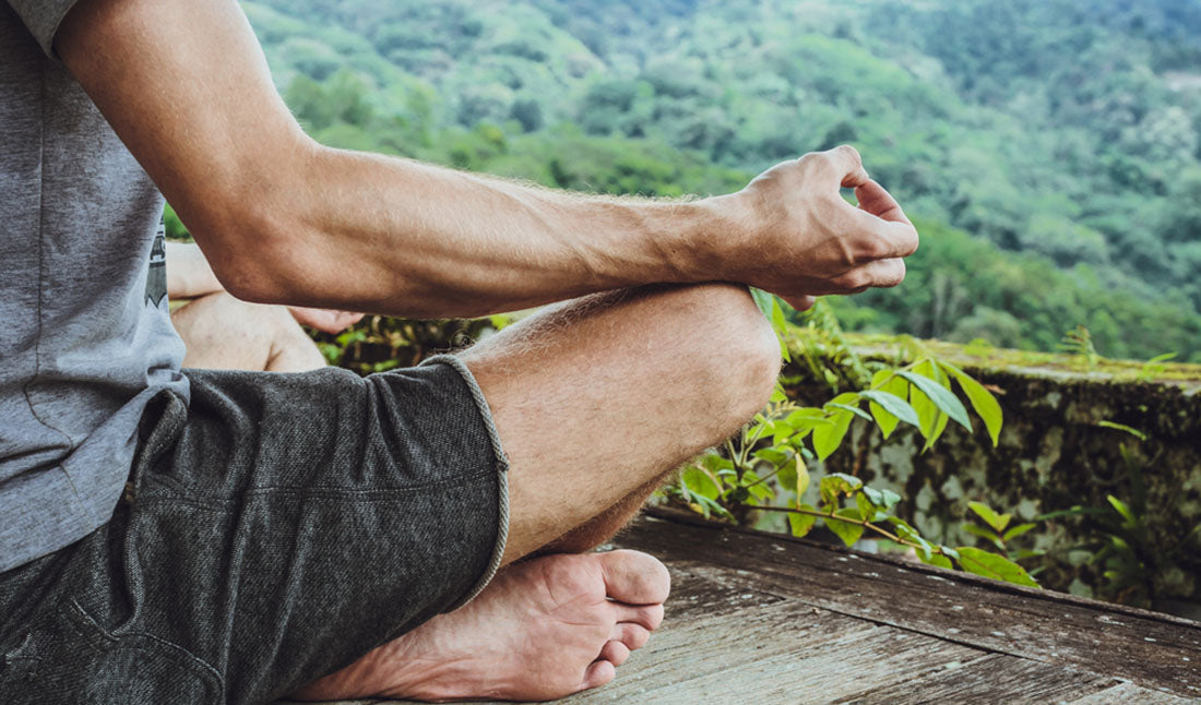 man meditating on deck in mountains