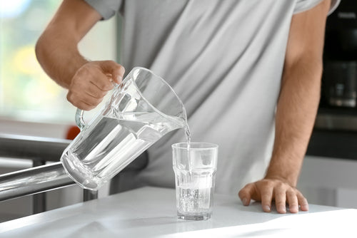 man pouring glass of water