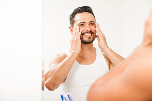 man placing moisturizer on face