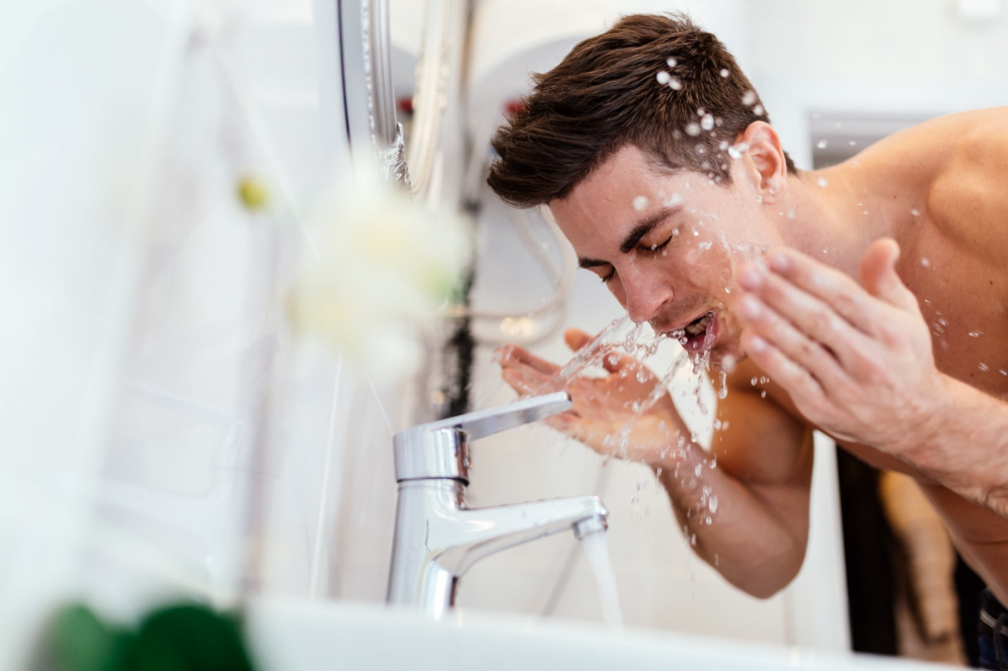 Man rinsing his face with water over the bathroom sink