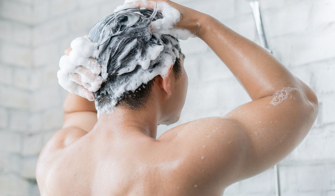 man shampooing hair in shower