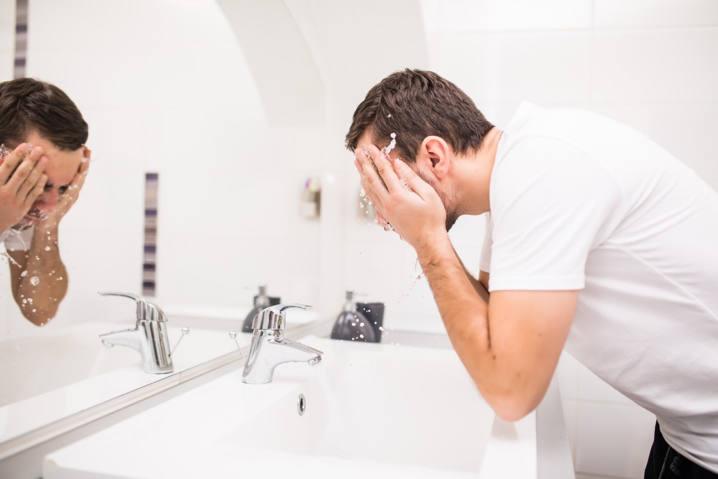 Man splashing water on his face over the bathroom sink