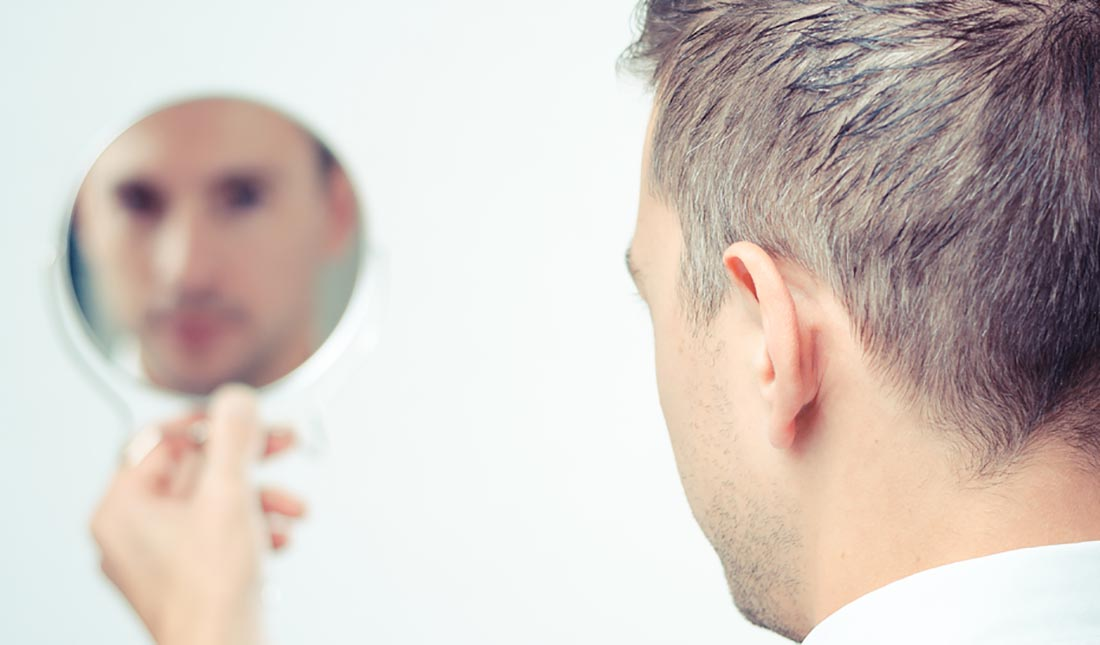 man staring into handheld mirror