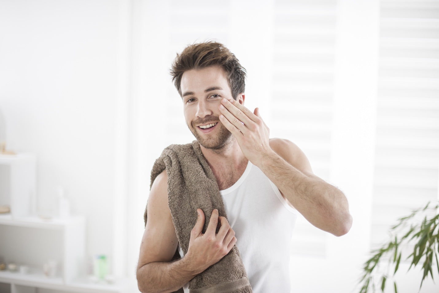 Happy man holding a towel applying face moisturizer