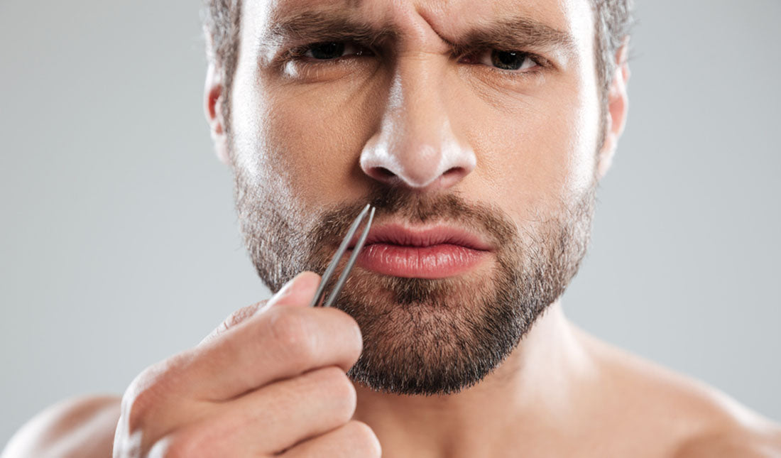man tweezing nose hairs