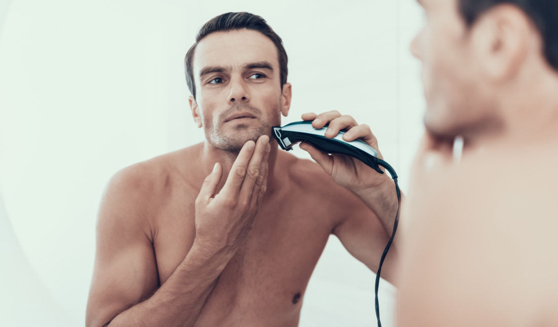 man using electric razor on face