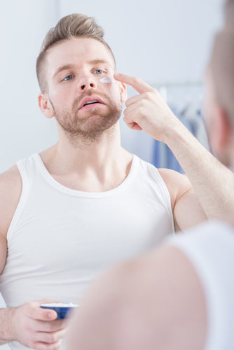 man using eye cream under eyes