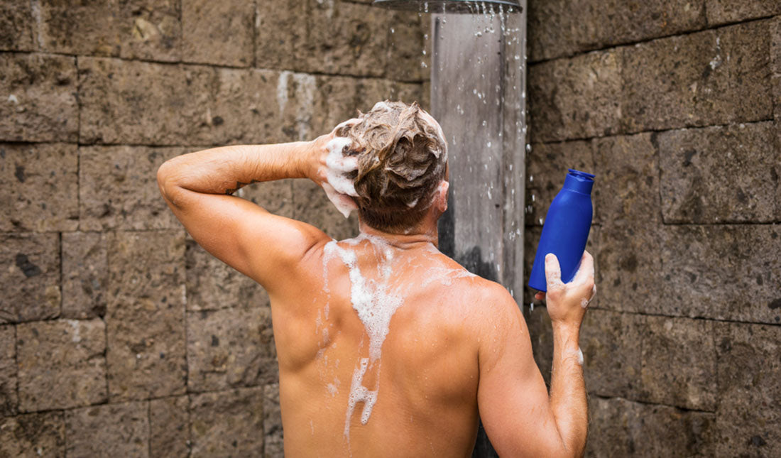 man using shampoo in shower