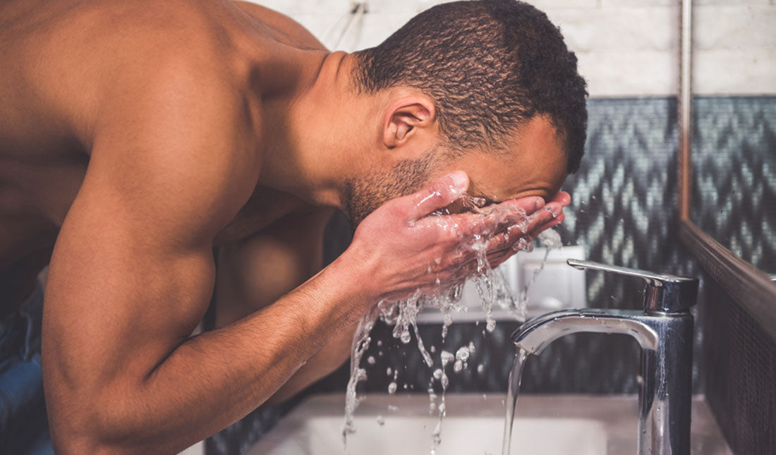Man washes face at bathroom sink