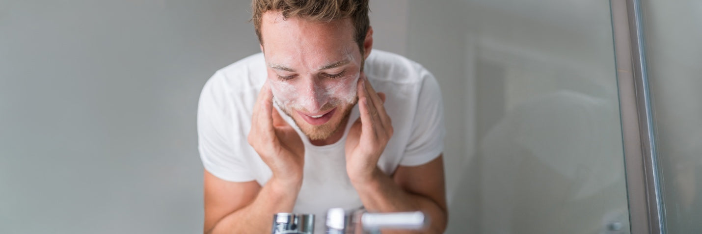 Man washing his face with an exfoliating scrub