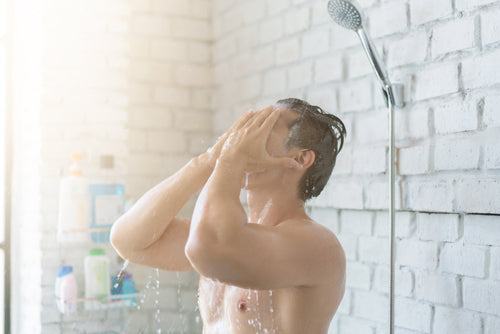 man washing face in shower