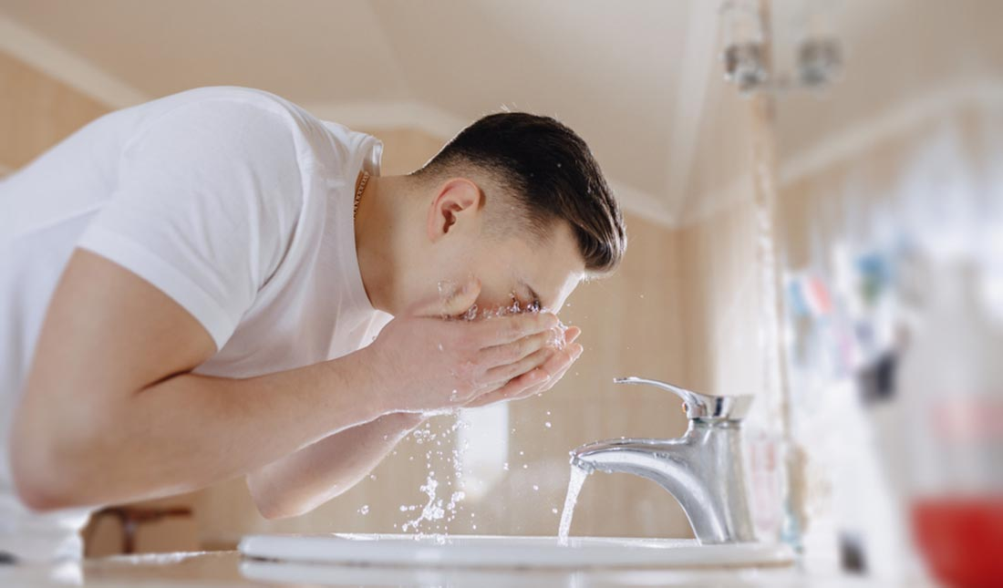 man washing face over sink