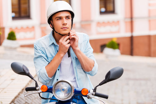 man on scooter placing helmet on head
