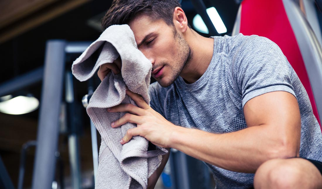 man wiping sweat gym