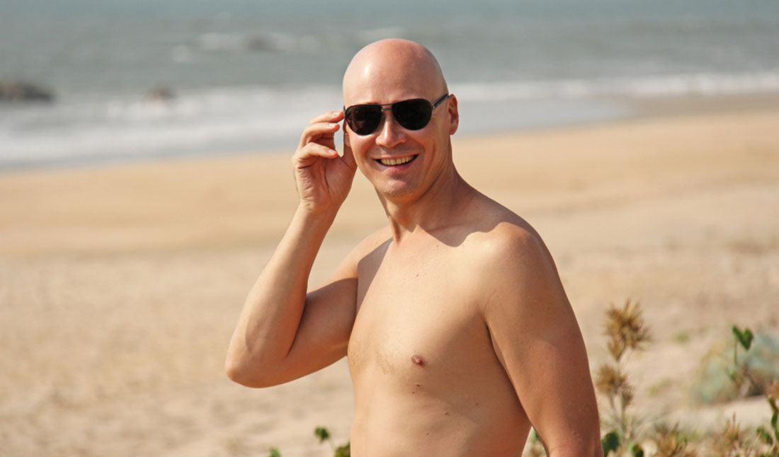 man with bald head at beach
