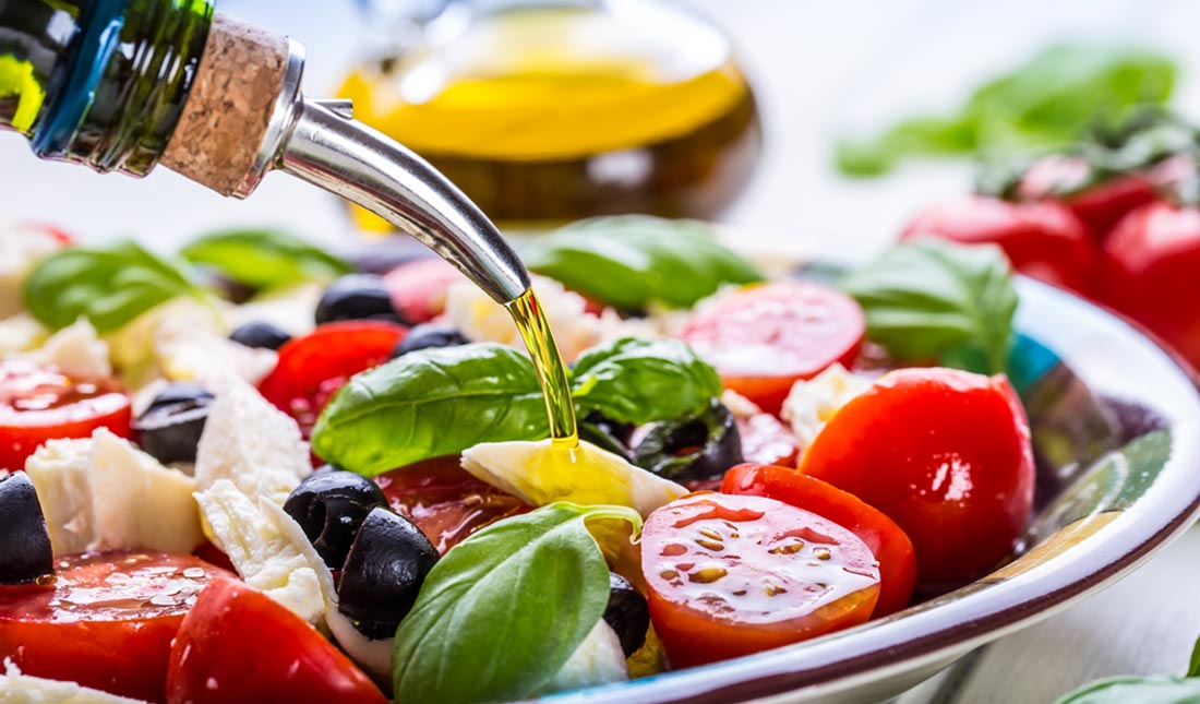 pouring dressing caprese salad