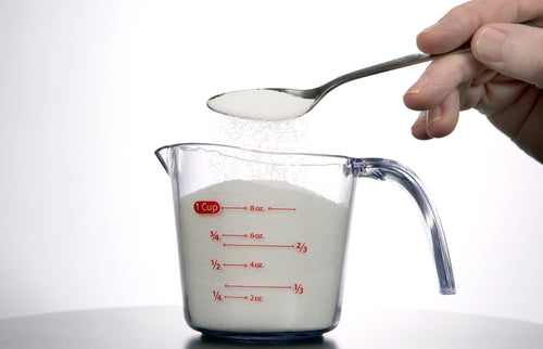 pouring sugar into measuring glass