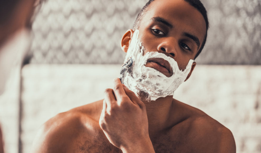shaving face with cream and razor