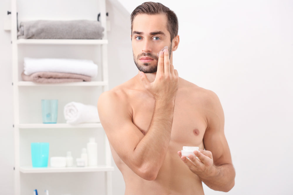 shirtless man applying face lotion