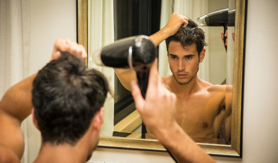 shirtless man blow drying hair