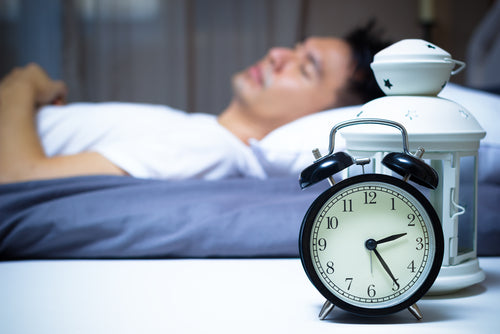 sleeping man with alarm clock