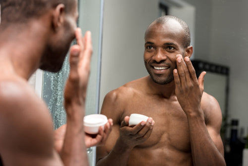 smiling man applying facial cream